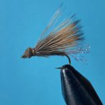 Photo of a X-Caddis fly pattern in a fly tying vice with a blue background