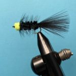 Photo of an Egg Sucking Leech fly pattern in a fly tying vice photographed on a blue background