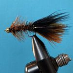 Photo of a Thin Mint fly pattern in a fly tying vice photographed on a blue background