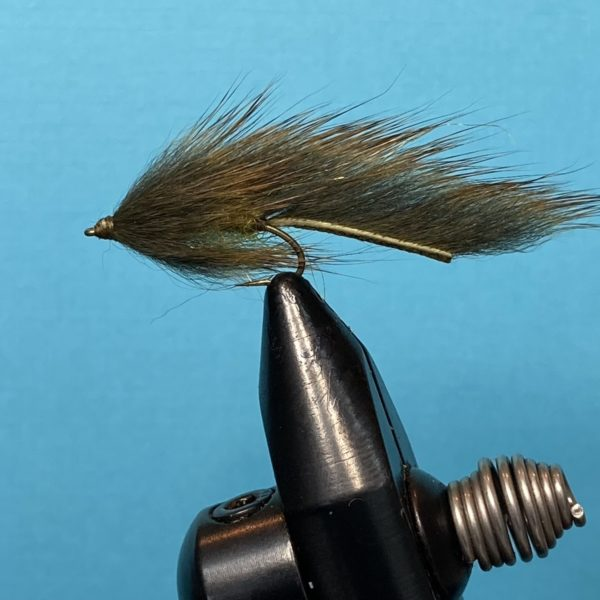 Photo of a Pine Squirrel Leech fly pattern in a fly tying vice photographed on a blue background